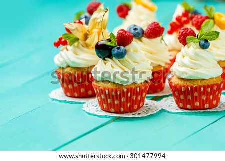 cupcakes with summer berries on blue wooden table - stock photo