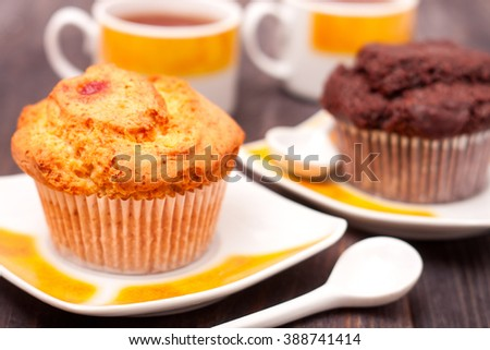 Cupcakes with tea on black wooden background