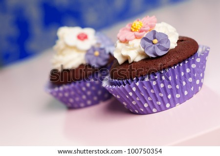 cupcakes with whipped cream topping and spring flower decoration - stock photo