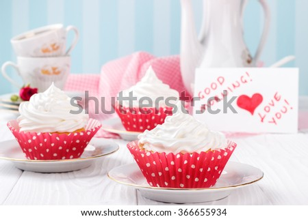 Cupcakes with white buttercream frosting on white wooden table with message Good morning