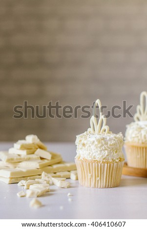 Cupcakes with white chocolate and coconut. White brick background.