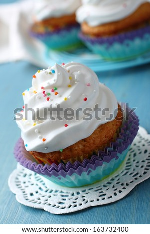 Cupcakes with white cream icing on blue wooden background - stock photo