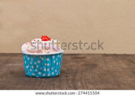 Cupcakes with white cream icing on wooden background - stock photo