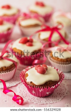 Cupcakes with white icing decorated with pink candy and ribbons. Selective focus