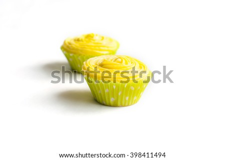 Cupcakes with yellow cheese cream in light green paper liners on white background. Selective focus - stock photo