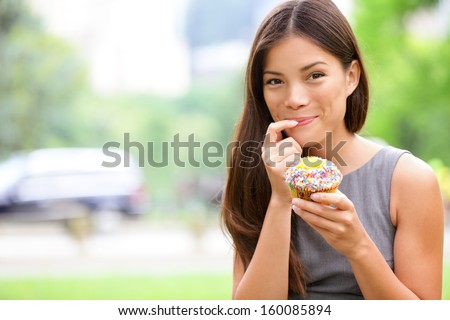 Cupcakes - woman eating cupcake in New York, Central Park, Manhattan. Business woman eating unhealthy food snack in lunch break smiling happy. Beautiful casual businesswoman in New York City, USA. - stock photo
