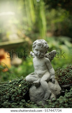 Cupid sculpture in garden, background for Valentine's day. Green color toned.