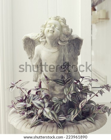Cupid statue and plant - stock photo