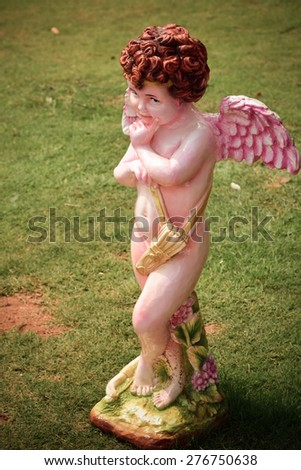 Cupid statue with  purple color wing. - stock photo