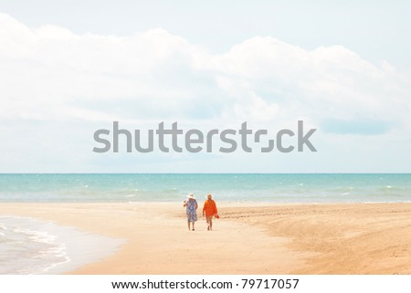 cuple of aged women walkin by the shore at the beach