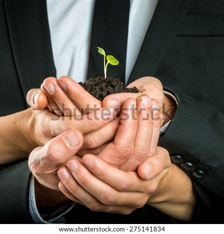 Cupped hands of different business people united to protect a green fragile sprout grown in fertile soil, concept of ecology and business start up. - stock photo