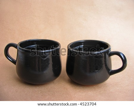 Cups and saucer on brown background - stock photo