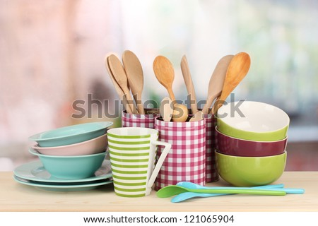 Cups, bowls nd other utensils in metal containers isolated on light background - stock photo