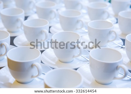 Cups for coffee and tea are seen at a table in restaurant - stock photo