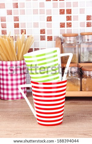 Cups in kitchen on table on mosaic tiles background - stock photo