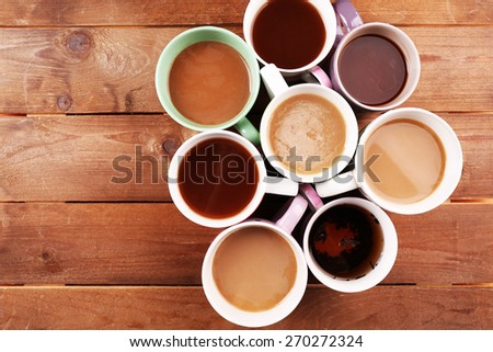 Cups of cappuccino on wooden table, top view - stock photo