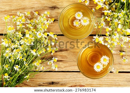cups of chamomile tea with chamomile flowers on wooden planks - stock photo