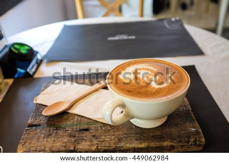 Cups of coffee on the wood table, latte art close up - stock photo