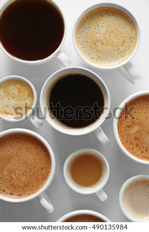 Cups of coffee on white background, top view
