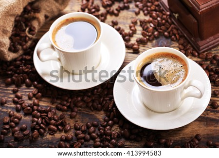 cups of coffee with beans on wooden table