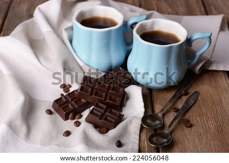Cups of coffee with chocolate and napkin on wooden table - stock photo