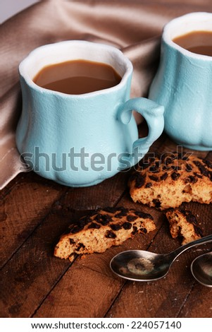 Cups of coffee with cookies and napkin on wooden table