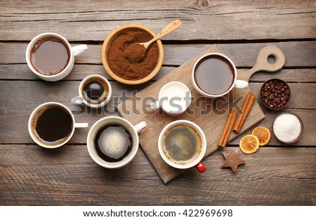 Cups of coffee with spices on wooden table, top view - stock photo