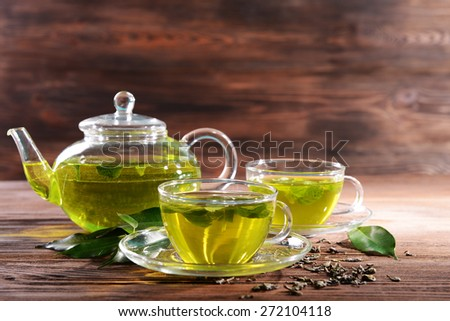 Cups of green tea on table on wooden background - stock photo