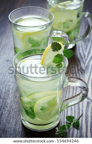 cups of green tea with mint, ginger root and a lemon