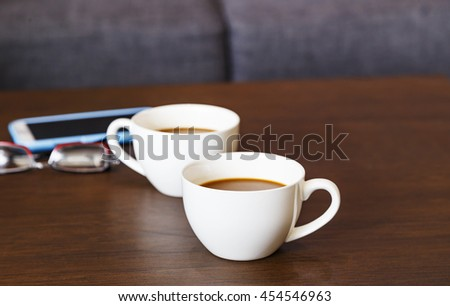 Cups of hot coffee on wooden table and glasses