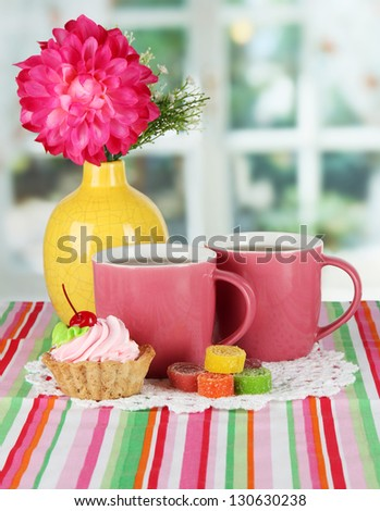 Cups of tea with cake,candy and flower on table in room - stock photo