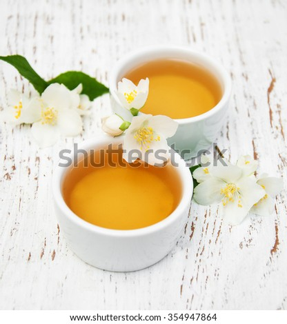 Cups of tea with jasmine flowers on a wooden background