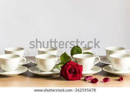 cups of tea with red rose, series,cups of tea with red rose,romantic moment in Italy, set on a wooden table with natural light on a white background  - stock photo