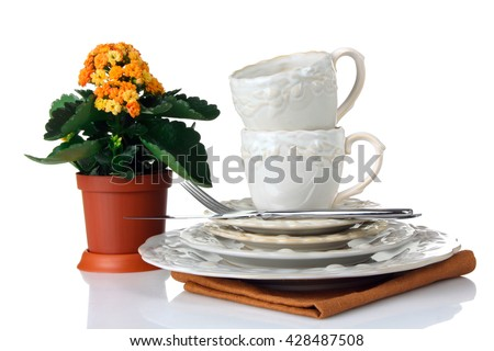 cups, plates and saucers on the cloth on a white isolated background with a flower and Cutlery - stock photo