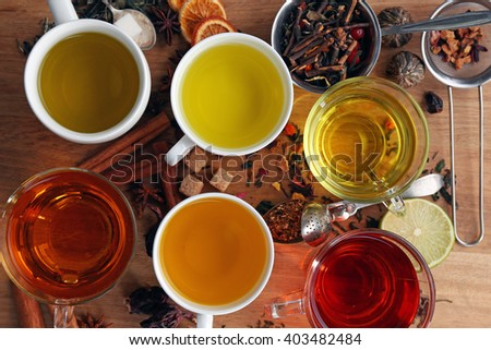 Cups with different kinds of tea and ingredients on table - stock photo