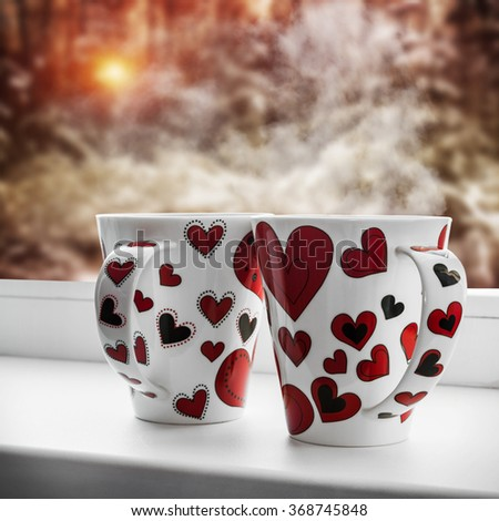 cups with hearts stands on a window sill   - stock photo