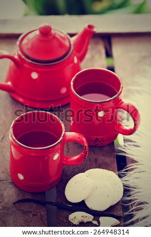 Cups with tea, teapot and cookies, vintage style - stock photo