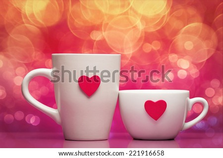 Cups with valentines day heart on pink background - stock photo