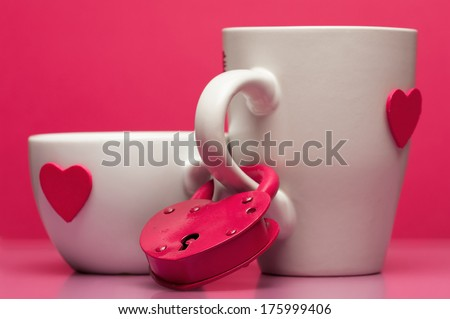 Cups with valentines day heart on pink background connected with padlock