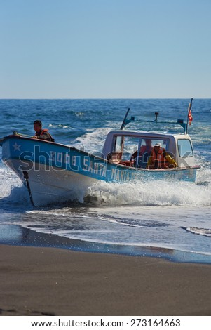 CURANIPE, CHILE - APRIL 22, 2015: Fishing boat coming ashore on the sandy beach in the fishing village of Curanipe, Chile. Once beached on the sand, a tractor pulls the boat to safer ground.