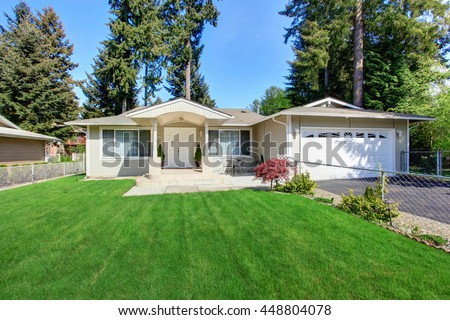 Curb appeal of beige house with well kept lawn and garage with driveway - stock photo