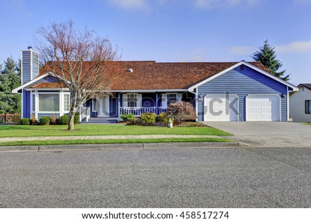 Curb appeal one level American house with blue and white trim and wooden porch. Also two garage doors and driveway. Northwest, USA