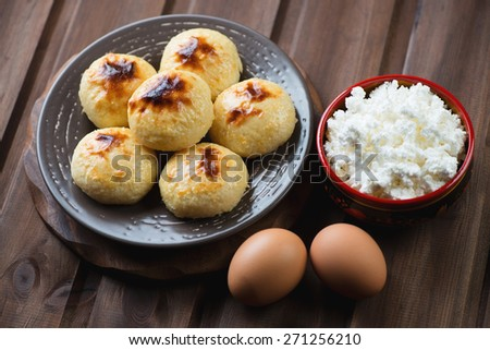 Curd pancakes over dark wooden background, studio shot, close-up - stock photo