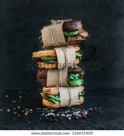 Cured chicken and spinach whole grain sandwich tower with spices and black stone background - stock photo