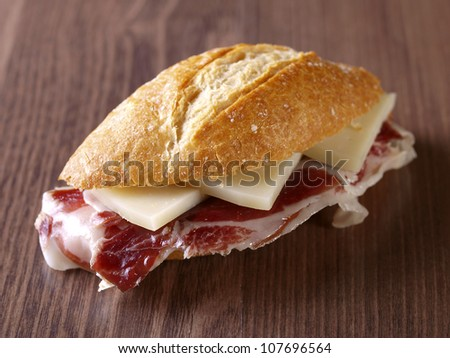 Cured ham and cheese sandwich. Typical spanish sandwich made with cured ham, cheese and baguette bread. - stock photo