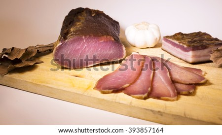 Cured meat on the wooden board  - stock photo