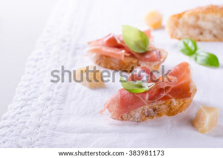Curied prosciutto on bread with cheese and basil on white background