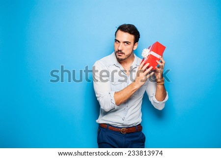 curious adult man checking a christmas gift on blue background - stock photo