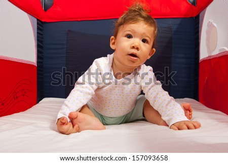 Curious baby boy sitting inside a playpen - stock photo
