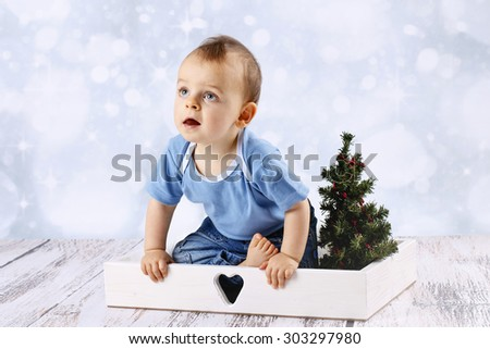 Curious baby boy waiting for Christmas - stock photo